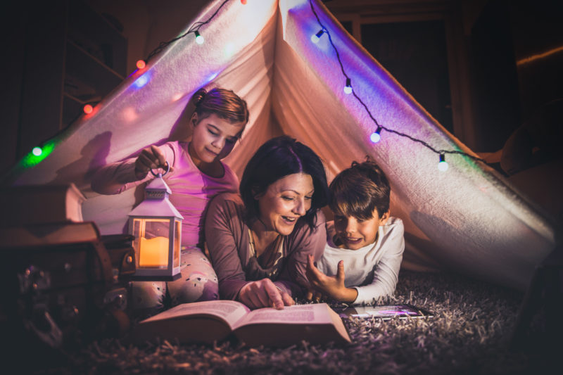 Happy family mother and child reading a book in tent at home